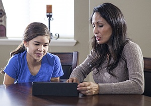 Woman and girl looking at tablet.