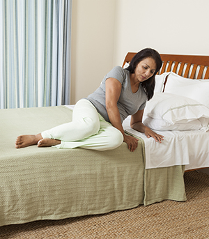 Woman on side in bed, getting ready to stand up.