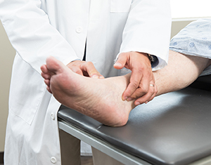 Closeup of healthcare provider examining man's foot.