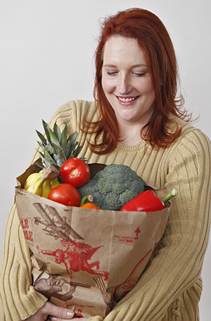 Woman holding grocery bag filled with fruits and vegetables.